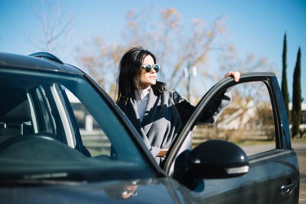 Empresária moderna em pé ao lado do carro Foto gratuita