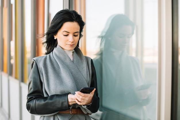 Empresária moderna usando smartphone ao ar livre Foto gratuita
