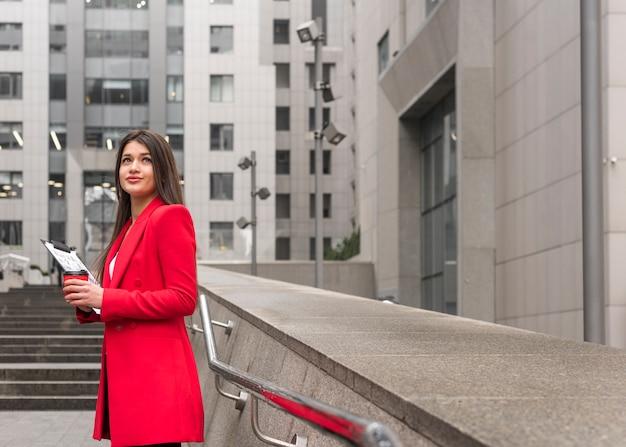 Empresária morena ao ar livre com casaco de leitura Foto gratuita