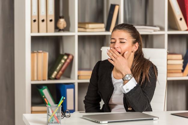 Empresária morena bocejando no escritório dela Foto gratuita