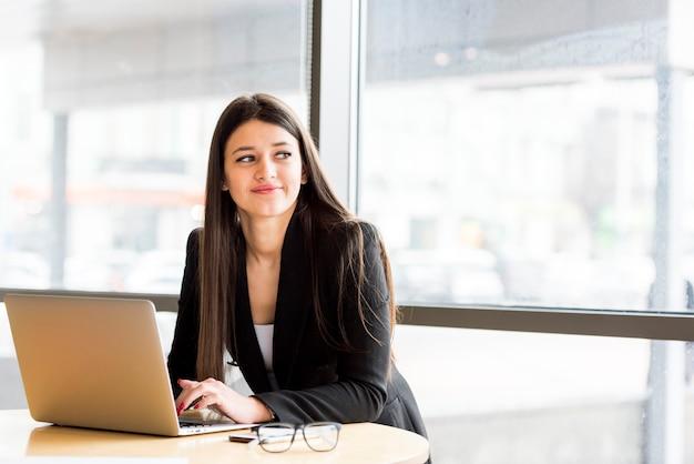 Empresária morena com laptop Foto gratuita