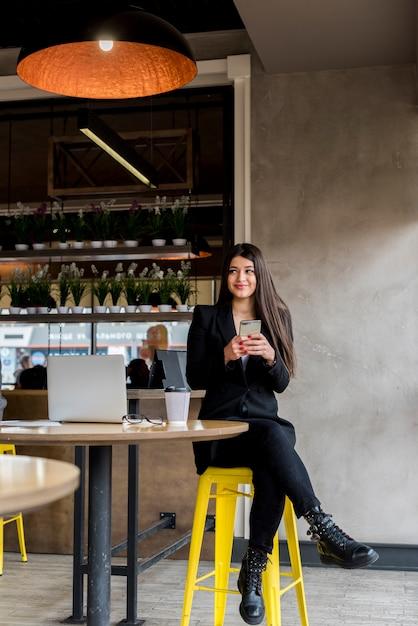 Empresária morena usando seu smartphone Foto gratuita
