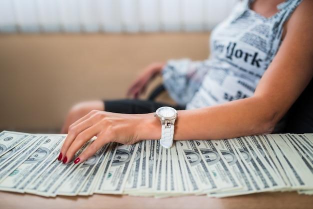 Empresária na mesa com dinheiro de suborno Foto Premium