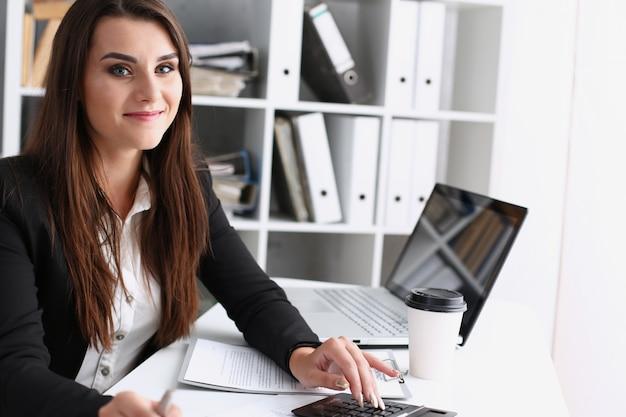 Empresária no escritório mantém a mão na calculadora Foto Premium