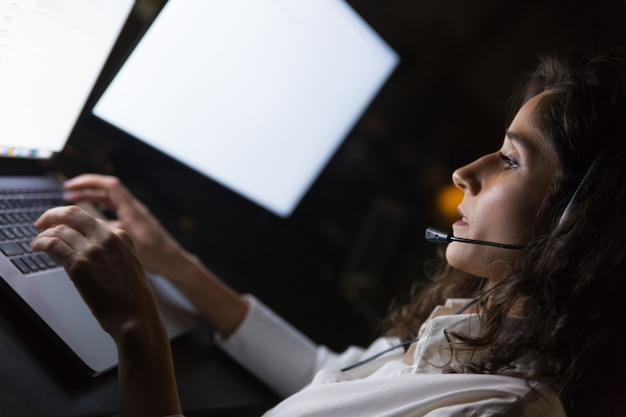 Empresária no fone de ouvido usando laptop Foto gratuita
