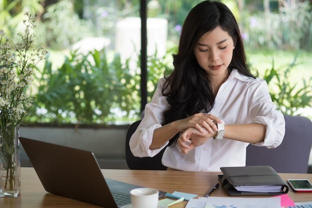 Empresária olha para o relógio dela. mulher verificar o tempo no relógio de pulso Foto Premium