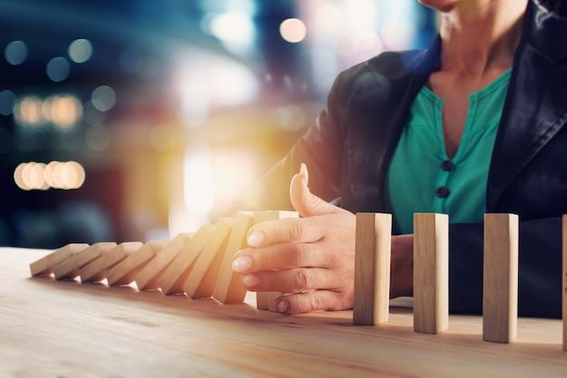 Empresária para uma cadeia cair como jogo de dominó. conceito de prevenção de crises e falhas nos negócios. Foto Premium