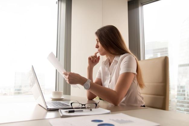 Empresária pensativa lendo o documento no escritório Foto gratuita