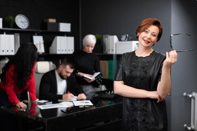 Empresária, segurando os óculos na camiseta dos trabalhadores de escritório, discutindo o projeto Foto Premium