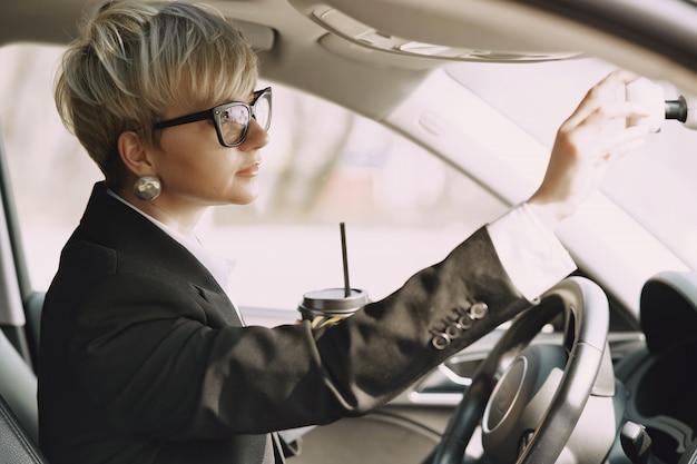 Empresária, sentado dentro de um carro e bebe um café Foto gratuita