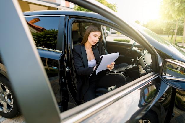 Empresária, sentado no carro com o notebook, falando no celular e fazendo anotações em papel. executivo feminino trabalhando em carro de luxo. Foto Premium