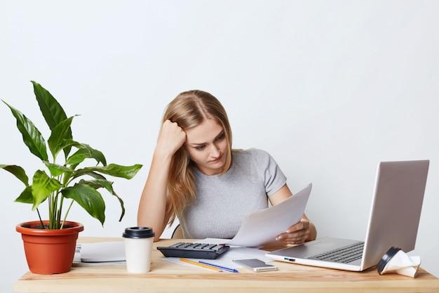 Empresária sobrecarregada, sentado à mesa de madeira, rodeada de aparelhos modernos, lendo documentos atentamente, tentando entender tudo. contador feminino que calcula contas e despesas Foto gratuita