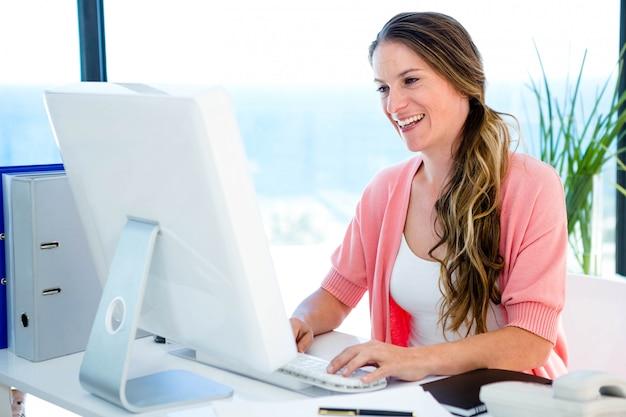 Empresária sorridente em seu escritório, no computador Foto Premium
