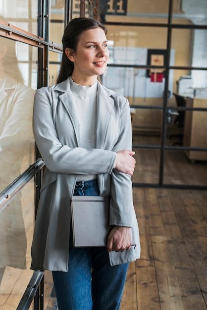 Empresária sorridente pensativa, apoiando-se na parede de vidro e segurando o diário no escritório Foto gratuita