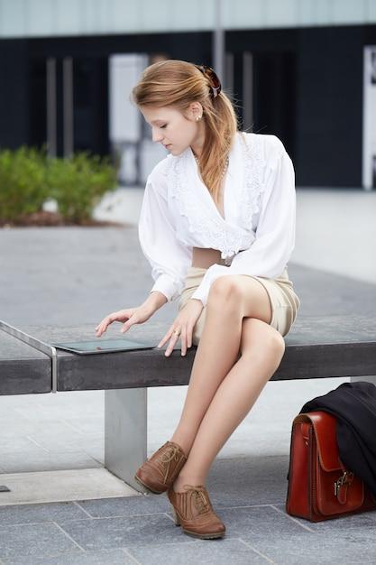 Empresária, trabalhando fora do prédio com dispositivos digitais Foto Premium