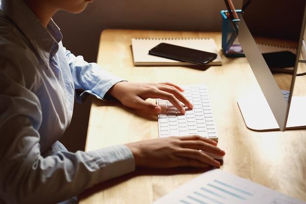 Empresária, trabalhando na mesa usando o laptop para verificar dados de finanças no escritório Foto Premium