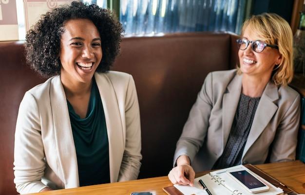 Empresárias alegres relaxantes em um café Foto gratuita