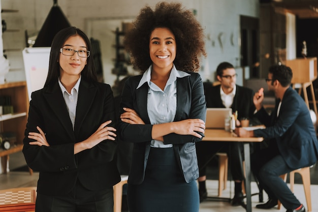 Empresárias asiáticas e afro-americanas com braços cruzados. Foto Premium