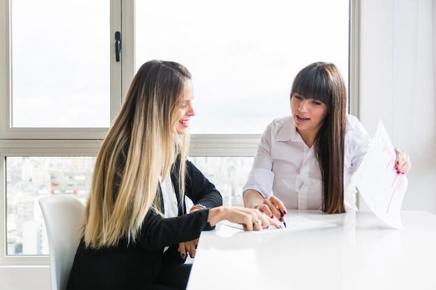 Empresárias, discutindo o plano de negócios no local de trabalho no escritório Foto gratuita