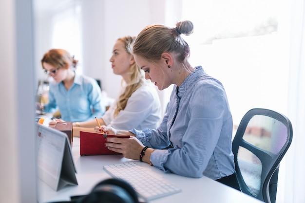 Empresárias, sentado em uma fileira, trabalhando no escritório Foto gratuita