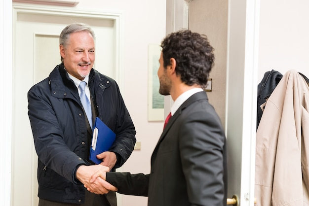 Empresário, acolhendo um convidado em seu escritório Foto Premium