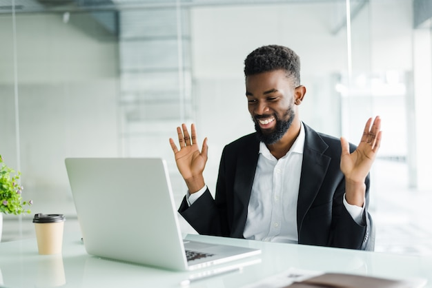 Empresário afro-americano chocado em fato se sentindo atordoado por notícias on-line, olhando para a tela do computador sentado no local de trabalho com laptop, investidor estressado comerciante surpreso com as mudanças do mercado de ações Foto gratuita