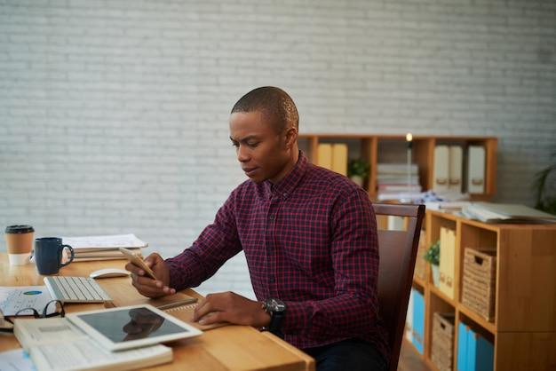 Empresário afro-americano com smartphone Foto gratuita