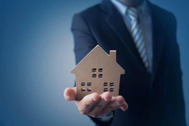 Empresário, agência banqueiro segurando modelo de casa e apresentar imóveis Foto Premium