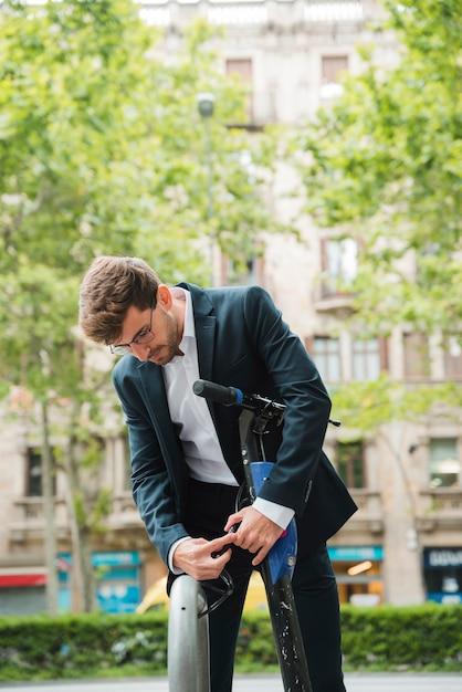 Empresário ajustando a alça de scooter elétrico Foto gratuita