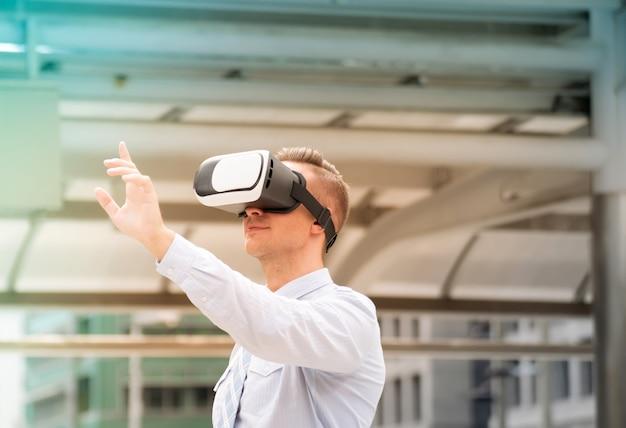 Empresário, ajustando o fone de ouvido de realidade virtual. homem usando fone de ouvido vr para trabalhar Foto Premium