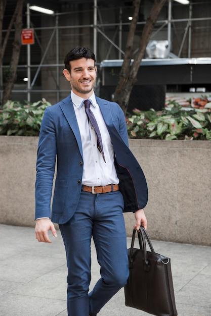 Empresário alegre andando na rua Foto gratuita