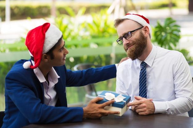 Empresário alegre dando caixa de presente para o colega Foto gratuita