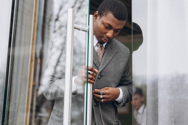 Empresário americano africano em terno cinza clássico, deixando o prédio de escritórios Foto Premium