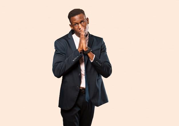 Empresário americano africano, sentindo-se preocupado, esperançoso e religioso, orando fielmente com as palmas das mãos pressionadas, pedindo perdão contra a parede bege Foto Premium