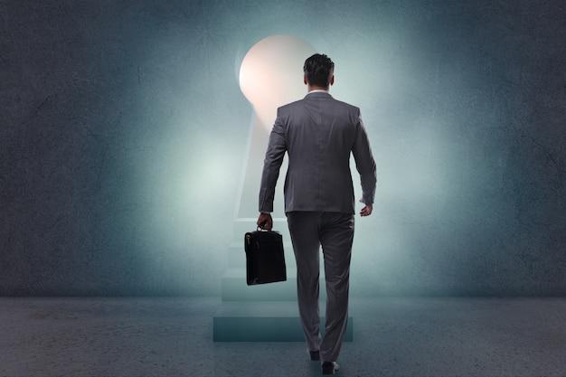 Empresário andando em direção a luz do buraco da fechadura Foto Premium
