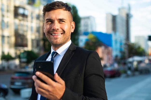 Empresário ao ar livre sorrindo e caminhando Foto gratuita