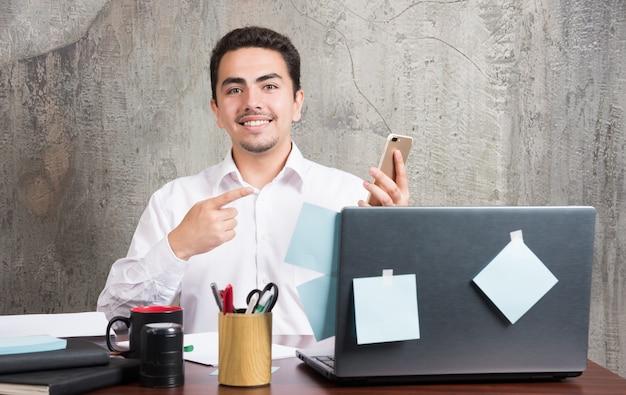 Empresário apontando alegremente o telefone para a mesa do escritório. Foto gratuita