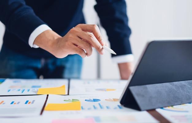 Empresário, apontando canetas digitais para tablet e trabalhando na mesa e documentos financeiros no escritório. Foto Premium