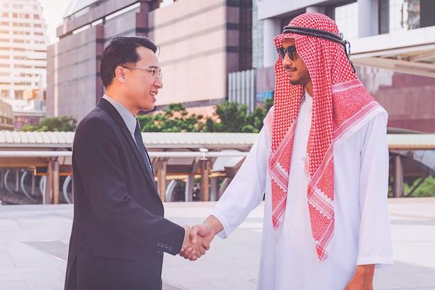 Empresário árabe dando um aperto de mão ao seu parceiro de negócios, no canteiro de obras Foto Premium