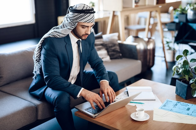 Empresário árabe no lapton no sofá no quarto de hotel Foto Premium