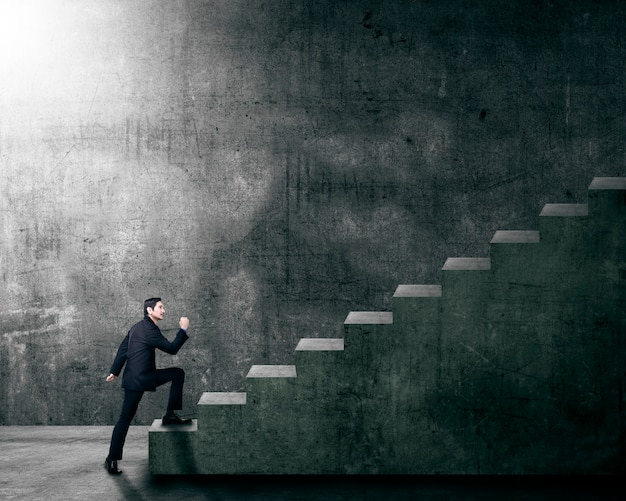 Empresário asiático atraente, intensificando uma escada Foto Premium