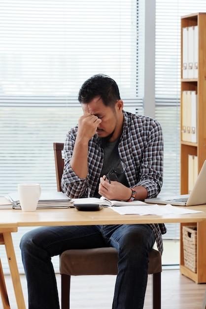 Empresário asiático cansado, sentado à mesa no escritório e esfregando a testa Foto gratuita