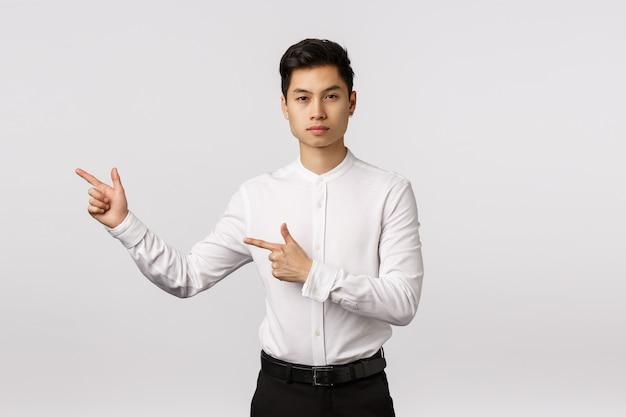 Empresário asiático de aparência séria dar direção, apontando para a esquerda Foto Premium