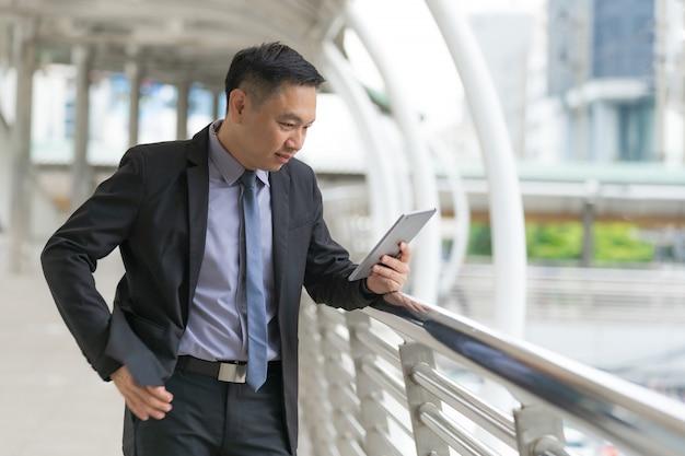 Empresário asiático em pé e segurando o tablet digital com prédios de escritórios de negócios Foto Premium