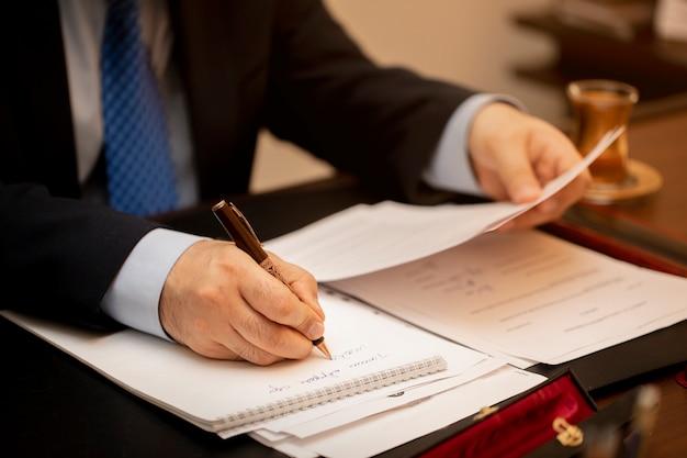 Empresário assinando papéis de contrato importantes Foto gratuita