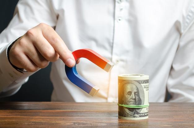 Empresário atrai dinheiro com um ímã. atrair dinheiro e investimentos para fins comerciais Foto Premium