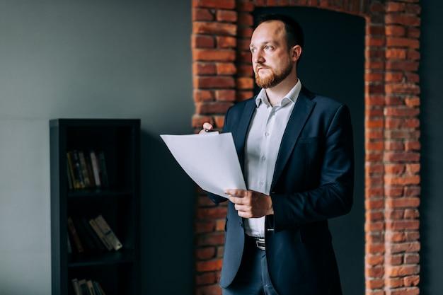 Empresário bem sucedido de terno fica e mantém um relatório financeiro em papel. Foto Premium