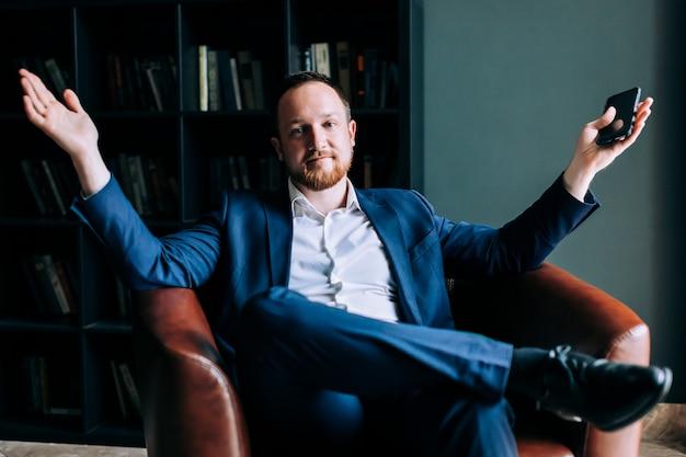 Empresário bem sucedido de terno se senta em uma cadeira de um escritório na moda. Foto Premium