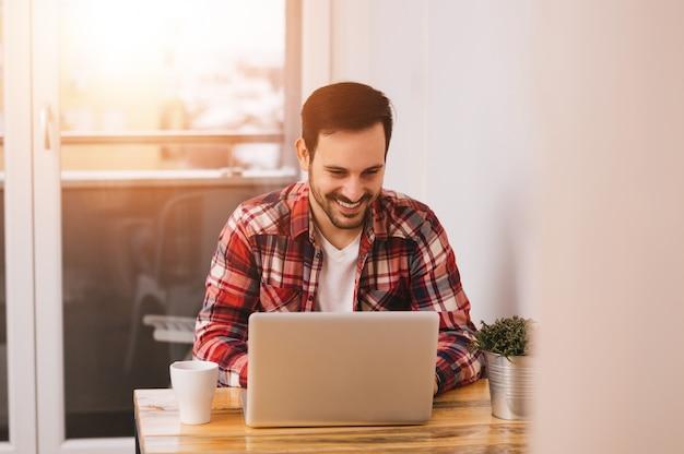 Empresário bem sucedido que sorri na satisfação como verifica a informação em seu laptop ao trabalhar em um escritório domiciliário. reflexo de lente Foto Premium