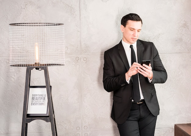 Empresário bonito com smartphone encostado na parede Foto gratuita